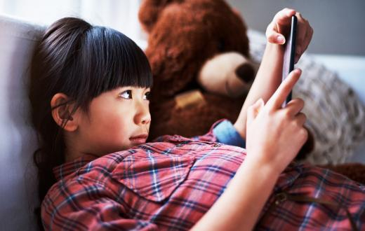 Girl at home looking at tablet sitting on couch with teddy bear beside her
