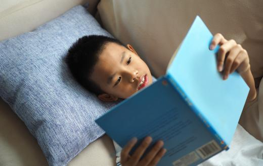 little boy lying on his back on the couch reading