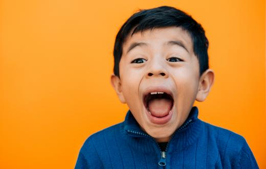 surprised happy little boy with a bright orange background