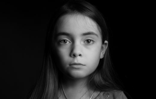 black and white photo of a serious girl partially in shadow looking at the camera