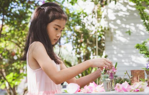 little girl playing with pink flowers