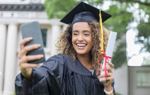 girl in a cap and gown taking a selfie alone