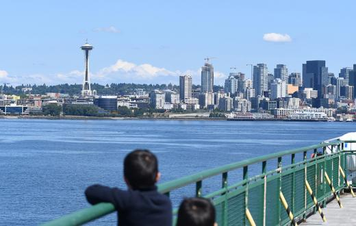 kids looking across the bay at the space needle from the deck of a ferry