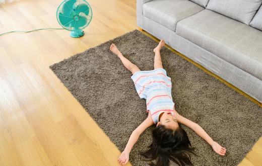 little girl lying on the floor in front of a fan