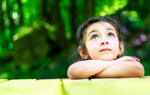 little girl outdoors leaning her crossed arms on a table looking up at the sky