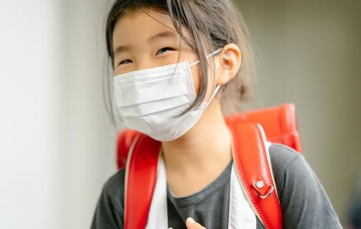 little girl wearing a backpack and a mask smiling with her eyes