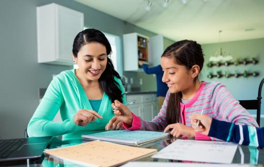 Mother helps her tween daughter with her homework at the kitchen table