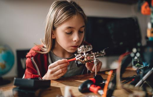girl learning robotics in her room at home with robot parts on her desk