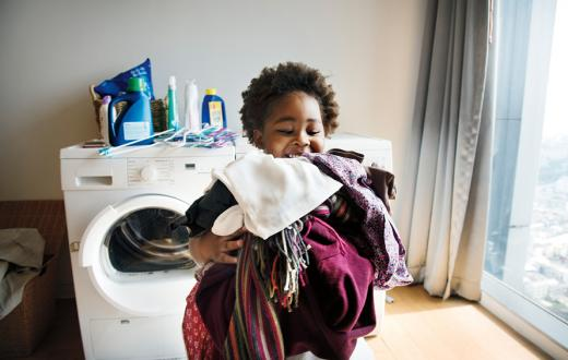 girl with an armful of laundry with the washer dryer in the background