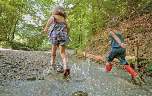 Girls running in the woods wearing rain boots on a warm wet fall day best weekend events kids seattle, bellevue, tacoma