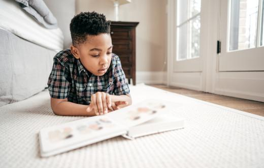 Young boy reads a book while lounging on the floor