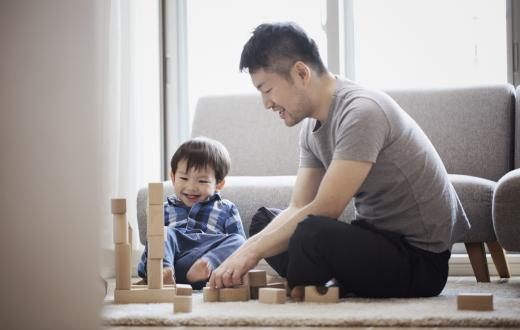 father and son playing with wood blocks on the living room floor