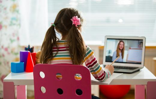 A young girl sits at her desk doing remote learning