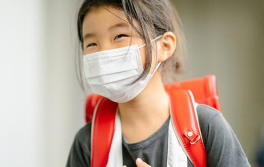 girl smiling under a face mask