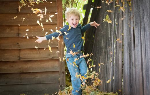 boy dancing in gold tumbling leaves with wooden buildings in the background