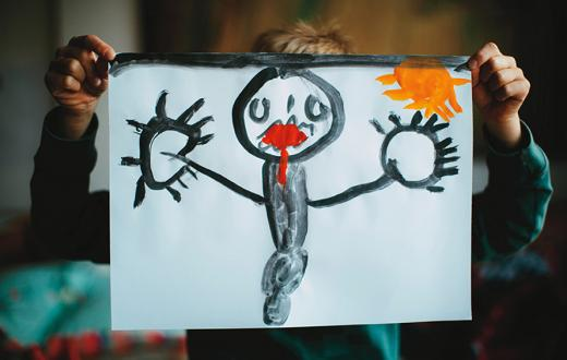kid holding up a drawing of a black figure with red lips and a yellow sun in the background
