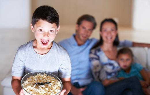 boy holding a bowl of popcorn with a plastic spider in it with his family on the couch in the background