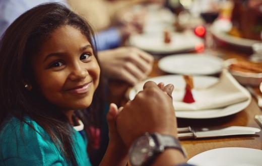 closeup of a girl at the dinner table holding her father's hand being thankful