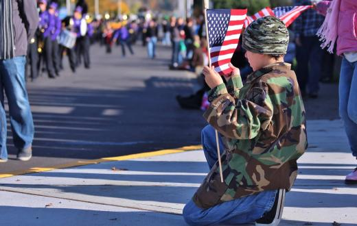 Boy-holding-flag-watching-veterans-day-parade-best-family-events-honor-veterans-2020-seattle-tacoma-bellevue-eastside-south-sound