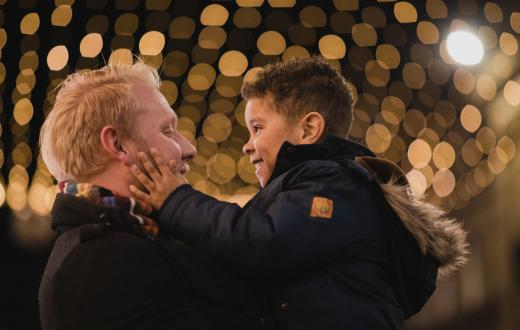Dad and son looking at each other happily with holiday lights in the background