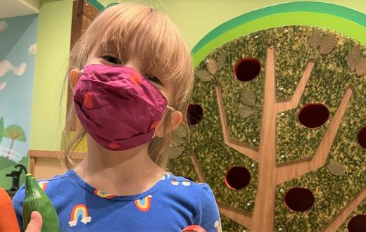Happy young girl wearing a face covering at KidsQuest Children's Museum in Belleuve reopening after pandemic closure