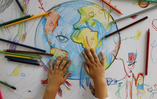 hand drawn globe with colored pencils and a kid's hands