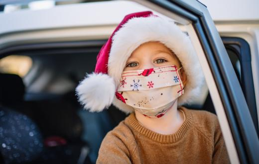 Little boy wearing protective face mask and Santa hat in car on Christmas
