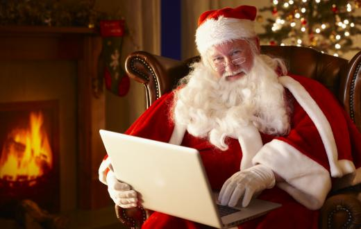 santa sitting in front of a fire holding a laptop