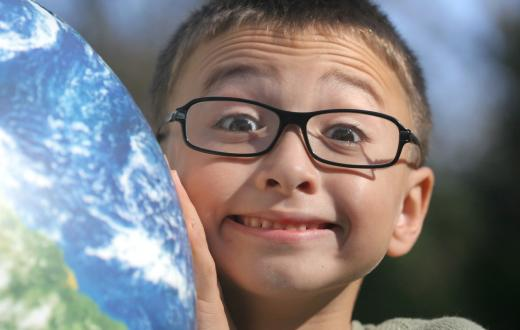 Cute boy with glasses holding up a globe