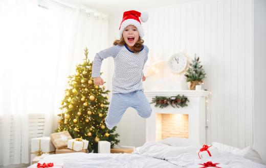 girl wearing a santa hat jumping on the bed