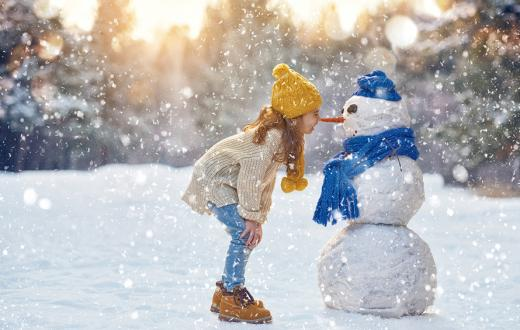 girl in a yellow hat bumping noses/carrot with a snowman wearing a blue scarf