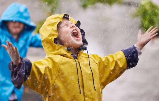 Kid wearing yellow rain jacket looking up at rain and smiling happily best backyard adventures for rainy season