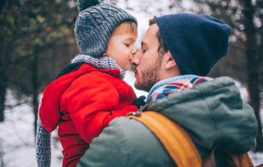 boy kissing his father's nose outside in the snowy woods