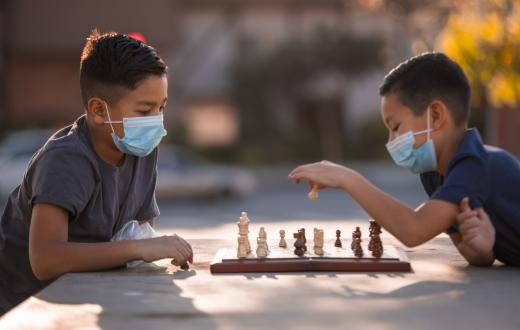 Two boys about age 10 or 11, wearing masks, sitting at a table outdoors playing chess in fall or winter