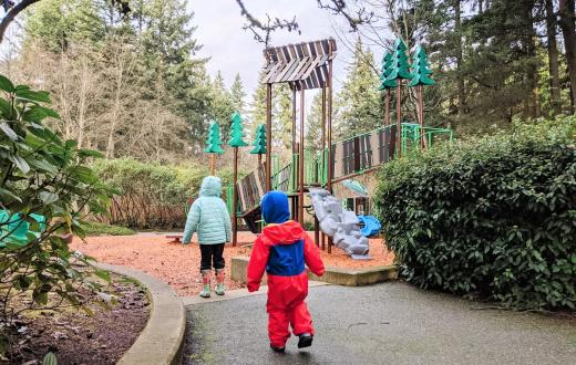 Young kids dressed for rainy weather approaching a new playground at Heron Park in Mill Creek, a small city near Seattle Washington