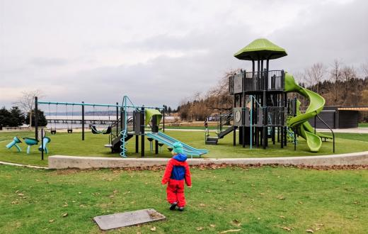 Small boy in red rain suit looking at new playground equipment installed at Kirkland's Juanita Beach Park near Seattle