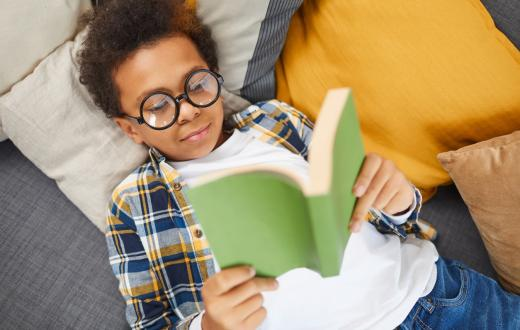 black boy with glasses reading a paperback