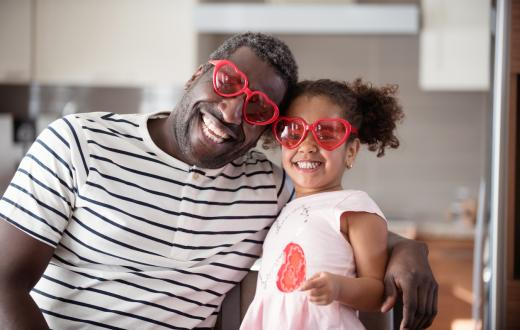 father and daughter smiling wearing heart shaped glasses for valentines day