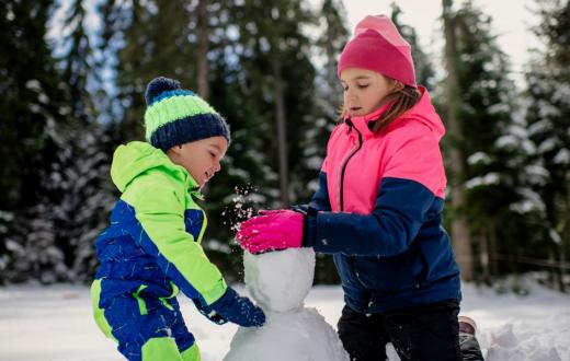 Brother and sister about ages 6 and 8 wearing snowsuits together build a snowman at new Seattle-area Sno-Park at Lake Easton along Interstate 90