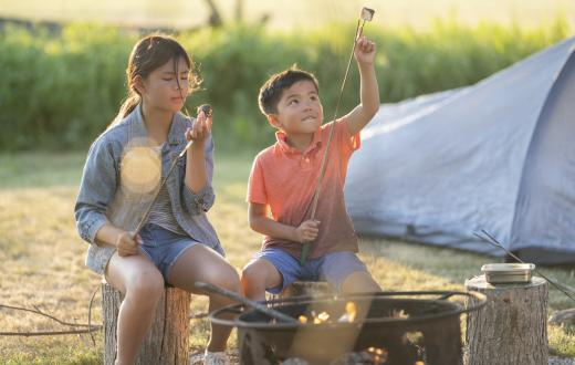 Two young siblings ages 9 and 6 roasting marshmallows by a campfire at a campsite with their tent in the background