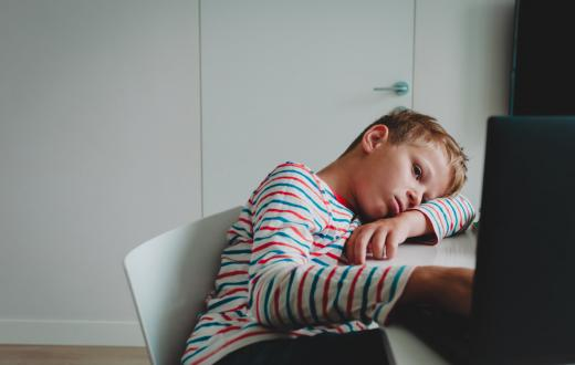 discouraged boy slumped on his desk in front of a computer