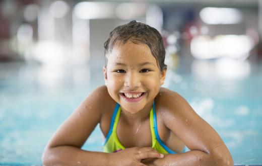 Elementary-age girl smiling, wearing swimsuit, with arms resting on the edge of an indoor swimming pool