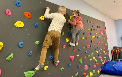 Two young kids wearing masks climb on an indoor climbing wall at Kaleidoscope Family Gym indoor play gym in Puyallup, Wash.