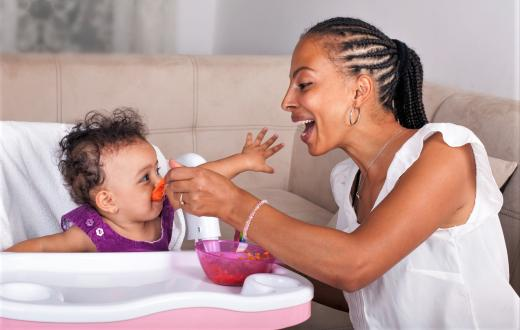 Black mom smiling and feeding baby in high chair with spoon in kitchen avoiding toxic ingredients in processed baby foods