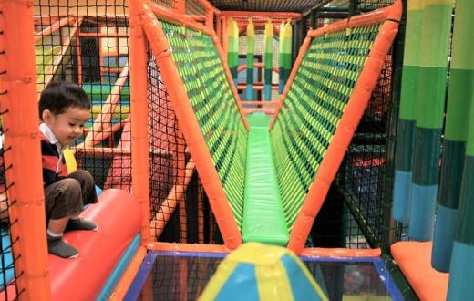 Small boy crouching in large colorful climbing structure at indoor play gym Safari inside Seattle's Southcenter Mall