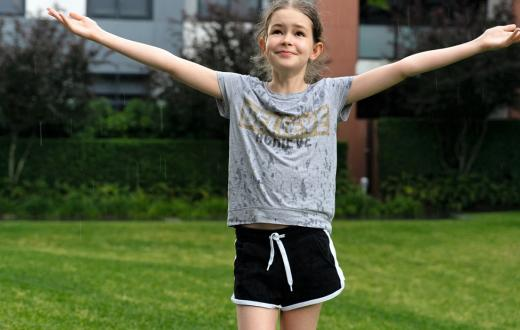 Happy tween girl with arms outstretched wearing shorts and t-shirt and standing in front of her school