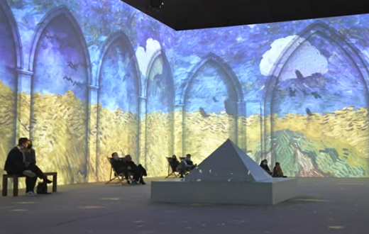 People in chairs watching Van Gogh The Immersive Experience video projections on the walls around them