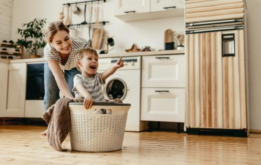 mom pushing her smiling son across the floor in a laundry basket