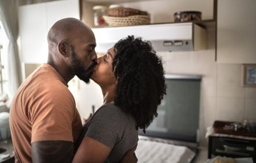 husband and wife kissing in the kitchen