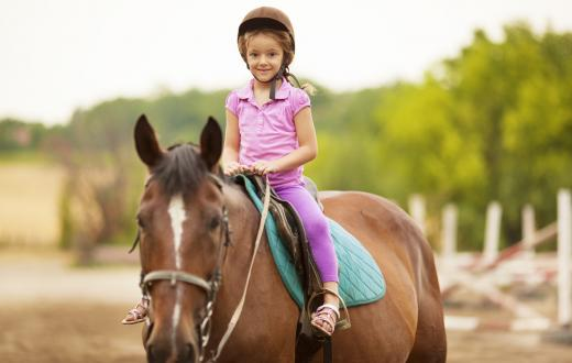 little girl riding a horse at horse camp